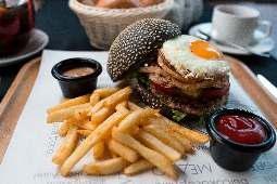 Черный бургер с куриной котлетой, луком фри, куриным яйцом и авторским соусом