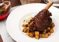 Баранья лытка тушеная с овощами в красном вине, подается с гарниром из картофеля