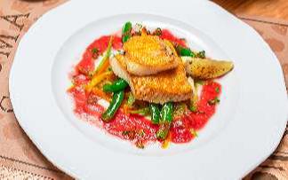 Филе палтуса запеченное с сыром пармезан на подушке из овощей с томатным соусом на подушке из овощей